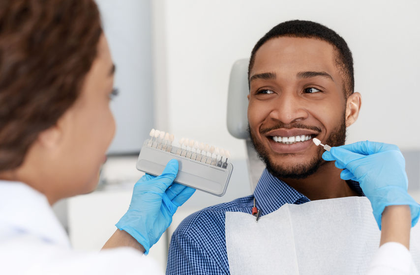 Female dentist choosing filling shade for smiling black guy, using tooth scale sample, close up